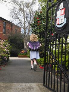 Elementary schoolgirl walking towards school building  bacの写真素材 [FYI03628915]