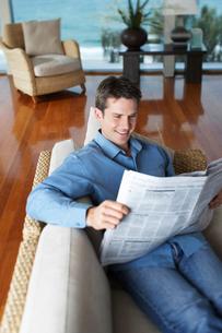 Man lying on sofa reading newspaper.の写真素材 [FYI03628930]