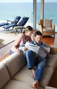 Couple reading newspaper at home  elevated view.の写真素材 [FYI03628931]