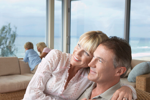 Wife sitting on husbands lap  arms around  on vacation neaの写真素材 [FYI03628963]
