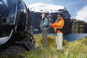 Man adjusting womans backpack next to helicopter on mountaの写真素材 [FYI03628988]