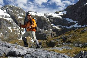 Hiker with walking sticks in mountainsの写真素材 [FYI03628993]