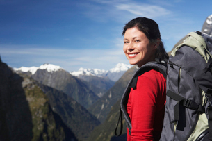 Female hiker wearing backpack on mountain peakの写真素材 [FYI03629002]