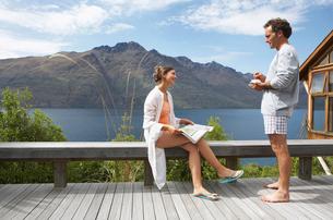 Couple in pajamas on balcony overlooking a mountain lakeの写真素材 [FYI03629007]