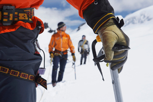 Hikers using walking sticks in snowy mountains  mid sectioの写真素材 [FYI03629023]
