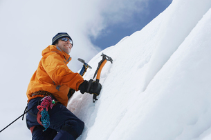 Mountain climber going up snow with axesの写真素材 [FYI03629030]