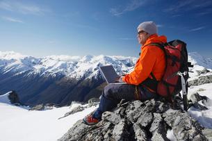 Mountain climber using laptop on mountain peakの写真素材 [FYI03629044]