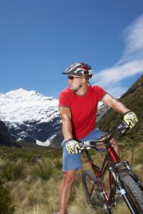 Cyclist sitting on bike in fieldの写真素材 [FYI03629054]
