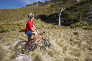 Cyclist looking at waterfall in fieldの写真素材 [FYI03629055]