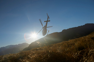 Helicopter flying over hills in front of the sunの写真素材 [FYI03629076]