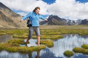 Woman walking barefoot through pond by mountainsの写真素材 [FYI03629083]