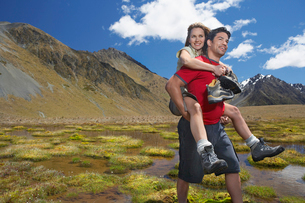Man giving woman piggy-back ride through pond near mountaiの写真素材 [FYI03629084]