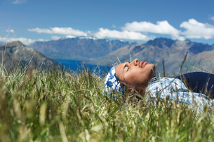 Man lying in field by lake and hillsの写真素材 [FYI03629087]