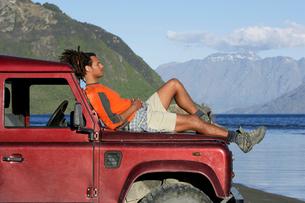 Man lying on hood of jeep near mountain lakeの写真素材 [FYI03629099]