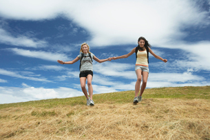 Two women holding hands skipping down hillの写真素材 [FYI03629107]