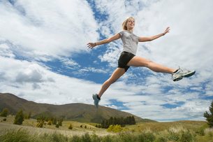 Woman leaping in hillsの写真素材 [FYI03629108]