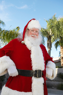 Smiling Santa Claus standing outside With Palm Treesの写真素材 [FYI03629117]