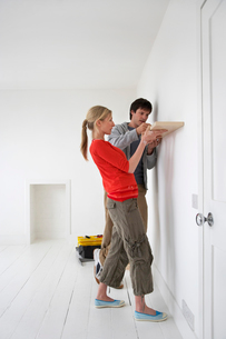 Couple putting up shelf in new homeの写真素材 [FYI03629119]