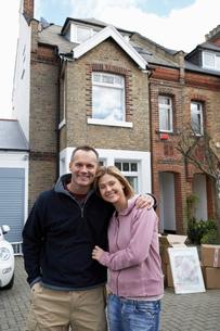Portrait of happy couple in front of houseの写真素材 [FYI03629125]
