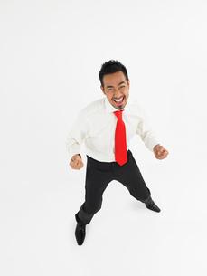 Man celebrating in studio  full lengthの写真素材 [FYI03629145]