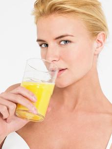 Young Woman in underwear Drinking Orange Juice  portraitの写真素材 [FYI03629198]