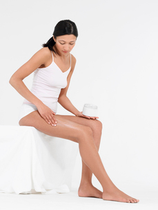 Young Woman in underwear Applying Body Lotion to thighsの写真素材 [FYI03629202]