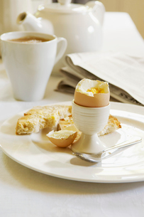 Half-Eaten Hard-Boiled Egg on dining room table  With Teaの写真素材 [FYI03629203]