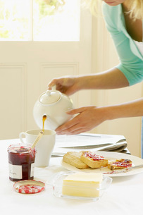 Woman Pouring Tea into cup on dining room table at Breakfaの写真素材 [FYI03629205]