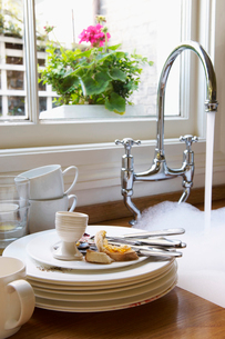 Stack of Dirty Dishes and silverware by Sink with runningの写真素材 [FYI03629211]