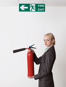 Businesswoman holding fire extinguisher under exit signの写真素材 [FYI03629231]