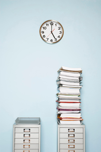 Office wall with clock  stack of paperwork in outbox on fiの写真素材 [FYI03629263]