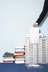 Man shredding document  close-up of hand  in officeの写真素材 [FYI03629265]