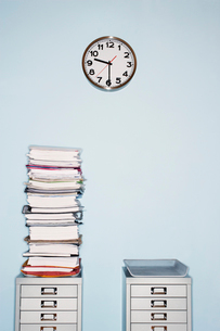 Office wall with clock  stack of paperwork in inbox on filの写真素材 [FYI03629266]