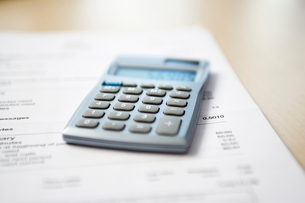 Calculator lying on telephone bill  close-upの写真素材 [FYI03629322]