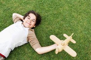 Smiling Pre-teen boy lying on back in grass  arm behind heの写真素材 [FYI03629337]