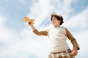 Low angle view of boy holding up wooden toy airplane againの写真素材 [FYI03629351]