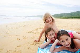 Children reclining  hand on cheek on beach towel on sandyの写真素材 [FYI03629357]