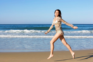 Young woman running on beach  side viewの写真素材 [FYI03629368]