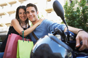 Young couple on motor scooter with shopping bags  portraitの写真素材 [FYI03629413]