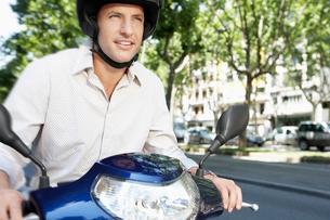 Mid-adult man riding motorscooter along city streetの写真素材 [FYI03629414]