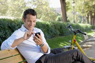 Businessman using palm pilot on park benchの写真素材 [FYI03629416]