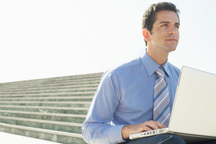 Young Business man sitting outdoors  using laptop.の写真素材 [FYI03629422]