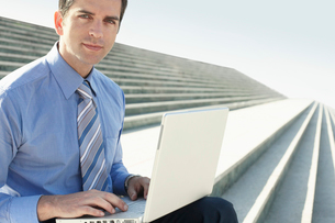 Young businessman sitting on steps  using laptop  portraitの写真素材 [FYI03629424]