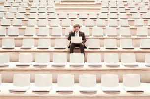 Businessman Using Laptop in Auditorium  front view.の写真素材 [FYI03629434]