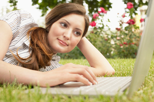 Young Woman lying on grass  using laptop.の写真素材 [FYI03629438]