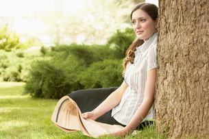 Woman sitting in grass  leaning on tree  holding newspaperの写真素材 [FYI03629444]