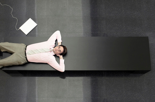 Businessman Lying down on Bench  view from aboveの写真素材 [FYI03629462]
