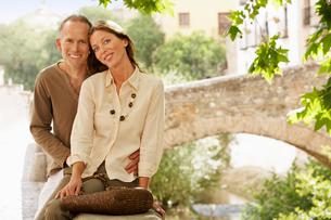 Tourist Couple sitting on wall by Stone Bridge  Granada  Sの写真素材 [FYI03629494]