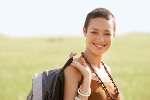 Female hiker holding backpack  standing in field  portraitの写真素材 [FYI03629504]