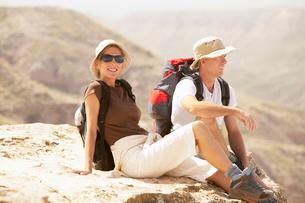 Hiking couple sitting on  mountainの写真素材 [FYI03629514]